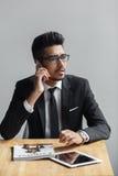 Przystojny młody biznesowy mężczyzna, opowiada na telefonie w kawiarni podczas gdy siedzący przeciw popielatemu tłu Zdjęcie Stock
