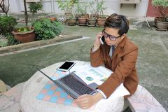 Przystojny młody biznesowy mężczyzna opowiada na telefonie z klientem Zdjęcie Stock