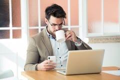 Przystojny młody biznesowy mężczyzna używa jego smartphone w biurze podczas gdy pijący kawę przed laptopem zdjęcia royalty free