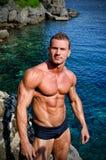 Przystojny młody bodybuilder bez koszuli oceanem lub morzem Zdjęcia Royalty Free
