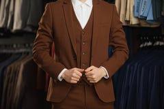 Przystojny młody brodaty biznesmen w klasycznym kostiumu Mężczyzna jest ubranym kurtkę Ja jest w sala wystawowej, próbujący na ub Zdjęcia Royalty Free