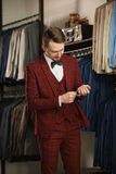 Przystojny młody brodaty biznesmen w klasycznym kostiumu Młody elegancki mężczyzna w kurtce Ja jest w sala wystawowej, próbuje na Obraz Stock
