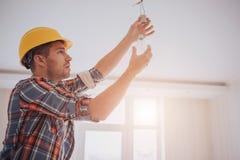 Przystojny młody budowniczy w żółtym budowa hełmie przekręca żarówkę wewnątrz Mężczyzna jest przyglądający up obrazy royalty free