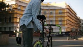 Przystojny młody caucasian mężczyzna iść na piętrze w przypadkowych ubraniach i słońc szkłach trzyma rower un jego ramię podczas  zbiory wideo