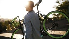 Przystojny młody caucasian mężczyzna w przypadkowych ubraniach i słońc szkłach trzyma rower podczas gdy iść downstairs outdoors w zbiory