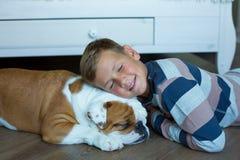 Przystojny Młody chłopiec dzieciak jest ubranym wygodne piżamy Bawić się z Jego angielskim śmiesznym byka psem na podłodze i cies fotografia royalty free