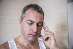 Przystojny młody człowiek dotyka jego głowę czuje silną migrenę z jeden ręką, zamyka w górę fotografii fotografia royalty free