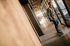 Przystojny młody człowiek jeździć na deskorolce w biurowym korytarzu Obrazy Stock