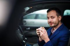 Przystojny młody człowiek je śpieszącego lunch w jego samochodzie Obraz Stock