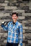 Przystojny młody człowiek jest ubranym kwadrata deseniowego błękit trzyma dalej jego ramię wysoki ciśnieniowy wodny pistolet na o Zdjęcie Stock