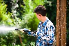 Przystojny młody człowiek jest ubranym kwadrata mienia wysokości deseniowego błękitnego naciska wodnego pistolet na ogrodowym tle Obraz Stock