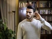 Przystojny młody człowiek może słuchać ` t, stawiający rękę wokoło jego ucho zdjęcie royalty free
