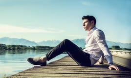 Przystojny młody człowiek na jeziorze w pogodnym, pokojowy obraz stock