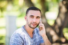 Przystojny młody człowiek opowiada na telefonie podczas gdy siedzący na ławce w parku fotografia royalty free