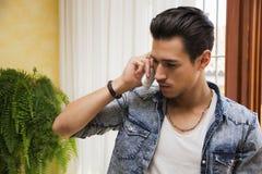 Przystojny młody człowiek opowiada na telefonu inside domu Fotografia Royalty Free