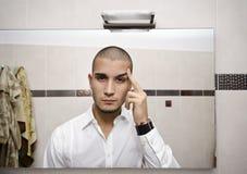 Przystojny młody człowiek patrzeje go w łazienki lustrze Obrazy Royalty Free