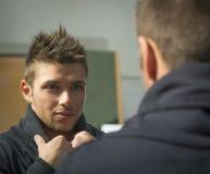 Przystojny młody człowiek patrzeje go w lustrze Zdjęcia Stock