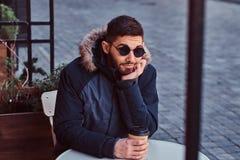 Przystojny młody człowiek pije kawę outdoors obraz royalty free
