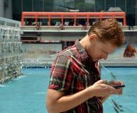 Przystojny młody człowiek podróżuje na Hong kong i patrzeje jego telefon komórkowego Obraz Stock