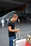 Przystojny młody człowiek podróżuje na Kyoto i patrzeje jego telefon komórkowego Zdjęcia Royalty Free