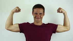Przystojny młody człowiek pokazuje jego bicepsy zbiory