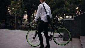 Przystojny młody człowiek przychodzący w białych koszula nd czerni troussers niesie trekking gren coloured rower i czerni podczas zdjęcie wideo