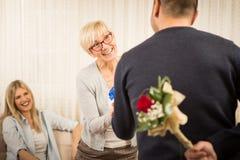 Przystojny młody człowiek przynosi kwiaty zdjęcia royalty free