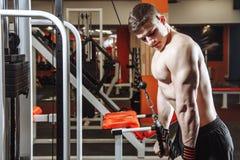Przystojny młody człowiek robi ćwiczeniom na bicepsach w gym Pojęcie sprawność fizyczna, sporty i zdrowy styl życia, obraz royalty free
