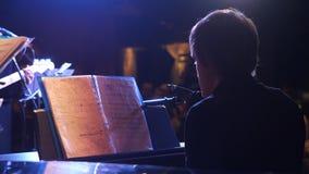 Przystojny młody człowiek robi fortepianowej muzyce, tylny widok Tylny widok bawić się pianino przy luksusowym hotelem muzyczny w Fotografia Royalty Free