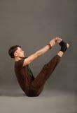 Przystojny młody człowiek robi joga nanavasana Fotografia Royalty Free
