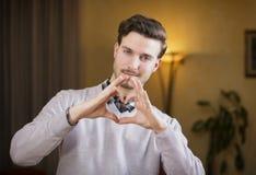 Przystojny młody człowiek robi sercu podpisywać z jego rękami Zdjęcie Stock