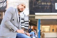 Przystojny młody człowiek siedzi na ławce w popielatym żakiecie i kapeluszu, odpoczywający, poj?cie miastowy zdjęcie royalty free