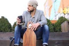 Przystojny młody człowiek siedzi pije kawę w popielatym żakiecie i kapeluszu z longboard, odpoczywający, Miastowy je?dzi? na desk zdjęcia royalty free