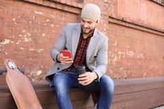 Przystojny młody człowiek siedzi w popielatym żakiecie i kapeluszowym używa smartphone z longboard, odpoczywający, Miastowy je?dz fotografia royalty free