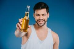 przystojny młody człowiek trzyma szklaną butelkę lata ono uśmiecha się i dink obrazy royalty free