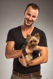 Przystojny młody człowiek trzyma Yorkshire teriera psa Zdjęcia Stock