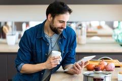Przystojny młody człowiek używa jego cyfrową pastylkę w kuchni podczas gdy pijący kawę w domu obraz royalty free