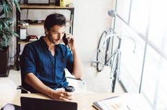 Przystojny młody człowiek używa smartphone przy drewnianym stołem podczas gdy siedzący przy pogodnym biurem zamazujący tło horyzo Obrazy Royalty Free