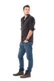 Przystojny młody człowiek w ciemnej szarawej szkockiej kraty koszula przyglądającej nad ramieniem z powrotem fotografia royalty free