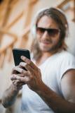 Przystojny młody człowiek w hełmofonach i okularach przeciwsłonecznych używać smartphone Obraz Stock