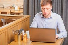 Przystojny młody człowiek w kawiarni Zdjęcia Stock