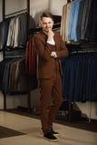 Przystojny młody człowiek w klasycznym kostiumu Ja jest w sala wystawowej, próbujący na ubraniach, pozuje Reklamowa fotografia Obraz Stock