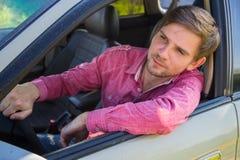 Przystojny młody człowiek w koszulowym jeżdżeniu samochód Obrazy Royalty Free