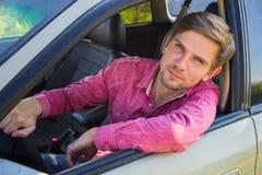 Przystojny młody człowiek w koszulowym jeżdżeniu samochód Obraz Stock