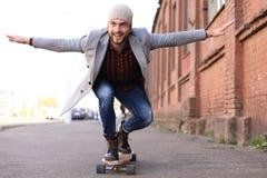 Przystojny młody człowiek w popielatym żakiecie i kapeluszu na longboard na ulicie w mieście Miastowy je?dzi? na deskorolce poj?c fotografia stock