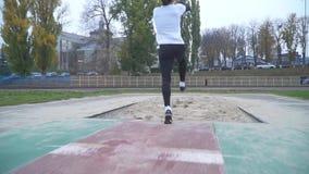 Przystojny młody człowiek w sportswear przyśpiesza i skoki w piaska piasku rozpraszają spod cieków bluza która zdjęcie wideo