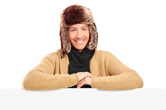 Przystojny młody człowiek z futerkowym kapeluszem pozuje behing panelu Obraz Stock