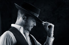 Przystojny młody człowiek z kapeluszowym czarnym tłem Obraz Royalty Free