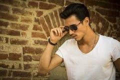 Przystojny młody człowiek z okularami przeciwsłonecznymi obok ściana z cegieł, outdoors zdjęcia stock