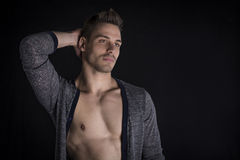 Przystojny młody człowiek z otwartym pulowerem na nagiej klatce piersiowej. zdjęcie stock